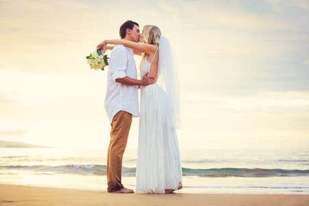 feier: Braut und Bräutigam beobachten Sonnenuntergang am schönen tropischen Strand, Romantische Paar-