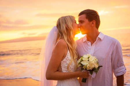 Net getrouwd paar zoenen op tropisch strand bij zonsondergang, Hawaii Beach Wedding