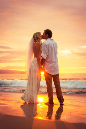 bridal couple: Just married couple kissing on tropical beach at sunset, Hawaii Beach Wedding, Intimate loving moment