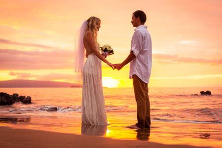 recien casados: Apenas pares casados ??en la playa tropical al atardecer, momento cari�oso �ntima en la boda Foto de archivo