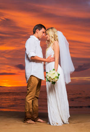 Just married couple on tropical beach at sunset, Intimate loving moment at wedding photo