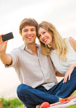 Couple taking photo of themselves with smart phone on romantic picnic date, taking a selfie photo