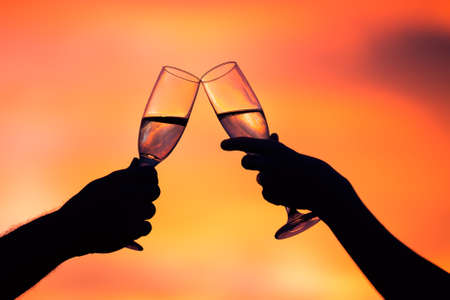champagne: Silhouette of couple drinking champagne at sunset