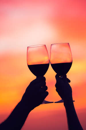 romance: Silhouette of couple drinking wine at sunset