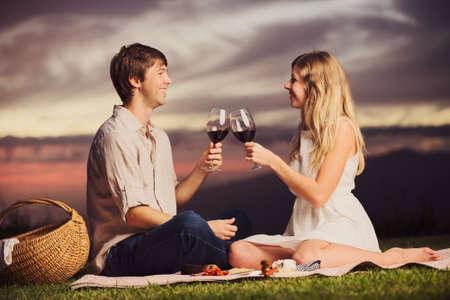 jovenes enamorados: Atractivo vaso pareja beber de vino en la comida campestre romántica puesta de sol