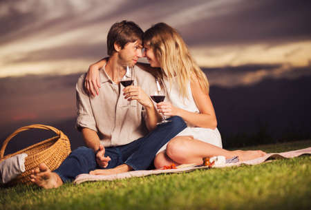 Attractive couple drinking glass of wine on romantic sunset picnic