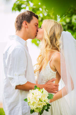 Just married couple kissing and embracing, Intimate loving moment at wedding photo