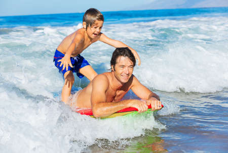 Father and Son Surfing Tandem Togehter Catching Ocean Wave, Carefree happy fun smiling lifestyle Stock Photo