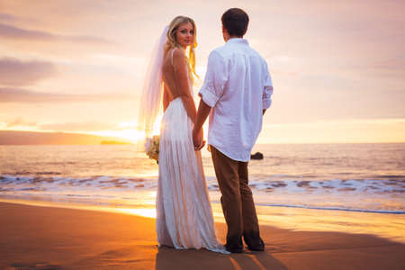 Married couple, bride and groom at sunset on beautiful tropical beach in Hawaii photo
