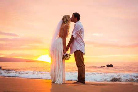 Married couple, bride and groom, kissing at sunset on beautiful tropical beach in Hawaii Banco de Imagens