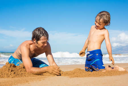 Father and son playing together in the sand on tropical beach, Building sand castle photo