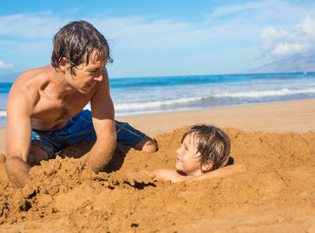Father and son playing together in the sand on tropical beach photo