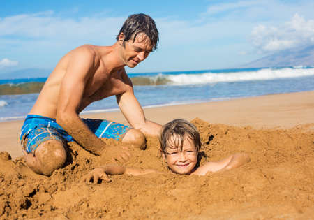 whites: Father and son playing together in the sand on tropical beach Stock Photo