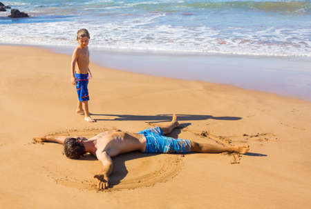 Father and son playing together in the sand on tropical beach on vacation photo