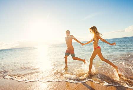 夕日、休暇で熱帯のビーチを走る幸せなカップル