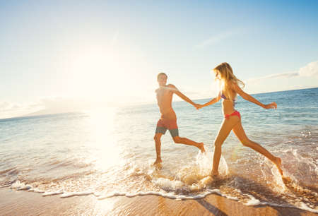 lovers holding hands: Happy Couple Running on Tropical Beach at Sunset, Vacation