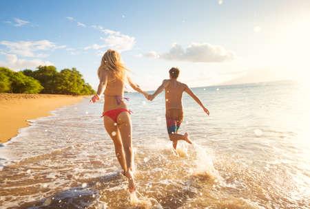 Pareja felices que se ejecutan en la playa tropical en la puesta del sol, vacaciones Foto de archivo