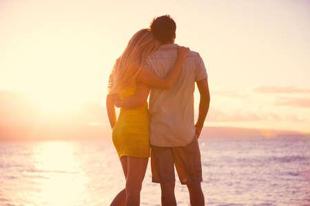 luna de miel: Feliz pareja romántica mirando el atardecer en la playa tropical de vacaciones