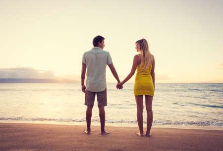 vacaciones playa: Feliz pareja rom�ntica mirando el atardecer de la mano en vacaciones Playa Tropical, Vintage Trendy color Styling Foto de archivo