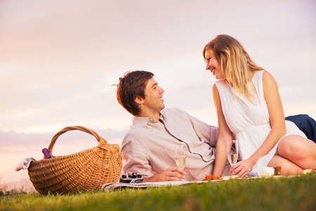 Attractive Couple Enjoying Romantic Sunset Picnic in the Countryside Stockfoto