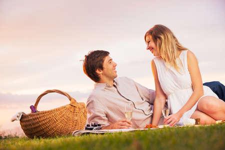 femme romantique: Attractive Couple Bénéficiant Coucher de soleil romantique de pique-nique dans la campagne