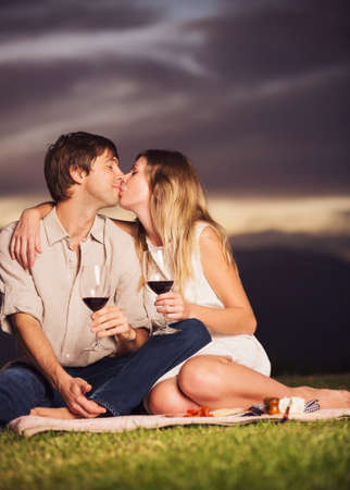 Attractive couple drinking glass of wine on romantic sunset picnic photo