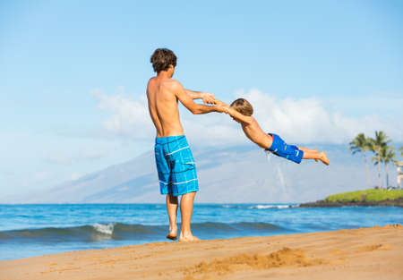 Happy father and daughter playing together at the beach carefree happy fun smiling lifestyle photo