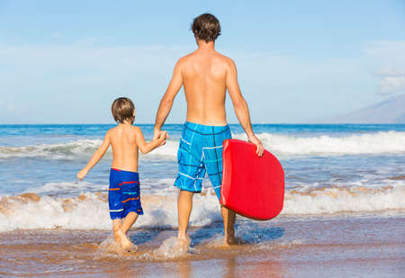 Father and Son Going Surfing Together on Tropical Beach in Hawaii photo