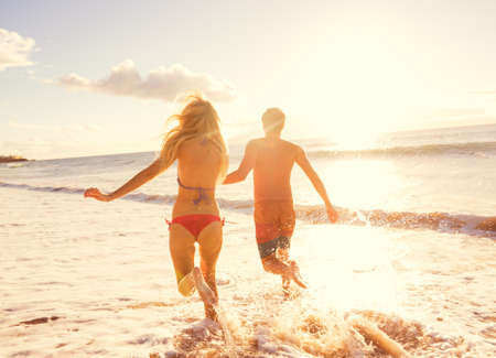 personas corriendo: Pares románticos que disfrutan Puesta de sol en Hermosa Beach Tropical Foto de archivo
