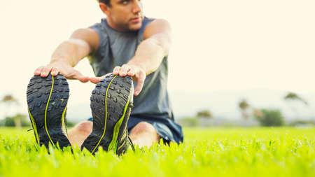 fitnes: Atrakcyjne pasuje młody człowiek rozciąganie przed ćwiczeniami