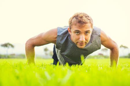Male athlete doing push up outside photo