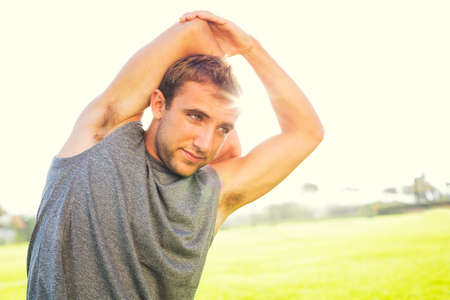 Attractive fit young man stretching before exercise workout