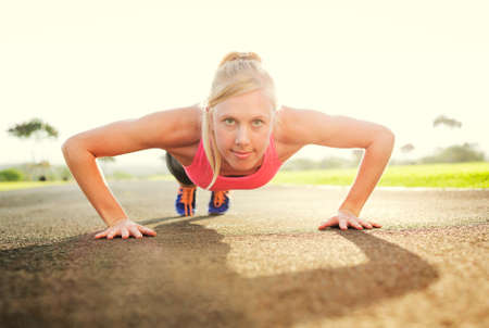Attractive young woman doing push up Foto de archivo