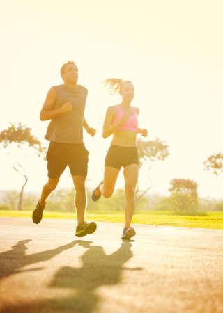Paar joggen loopt buiten in het park bij zonsopgang Stockfoto