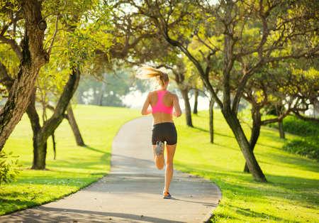 アスレチック公園で屋外早朝ランニング、ジョギングする若い女性に合う