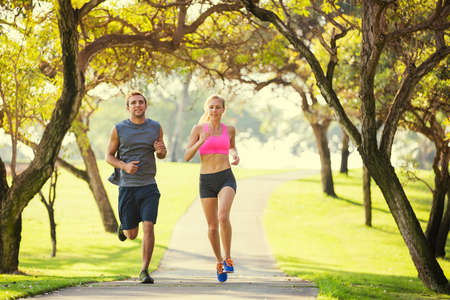 Couple jogging running outside in the park at sunrise on beautiful path