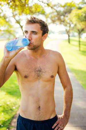shirtless guy: Portrait of athletic young man drinking water after workout outdoors