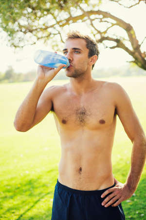 body builder: Portrait of athletic young man drinking water after workout outdoors