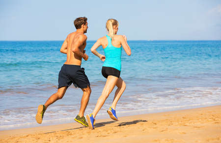 run out: Couple Sport runners jogging on beach
