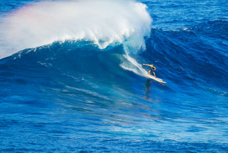Extreme surfer riding giant wave