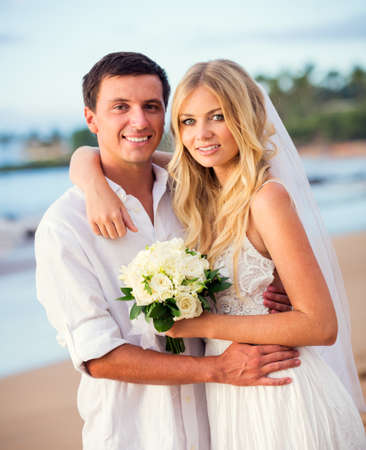 A married couple, bride and groom, at sunset on a beautiful tropical beach photo