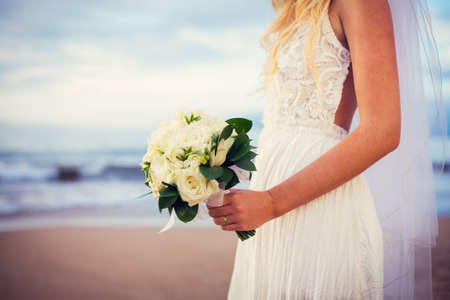 Portrait of beautiful bride standing by the beach at sunset Stok Fotoğraf
