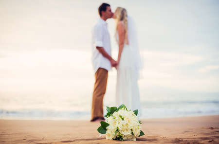 bride: A married couple, bride and groom, at sunset on a beautiful tropical beach, shallow depth of field focus on flowers