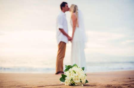 Een echt paar, bruid en bruidegom, bij zonsondergang op een prachtig tropisch strand, ondiepe scherptediepte focus op bloemen