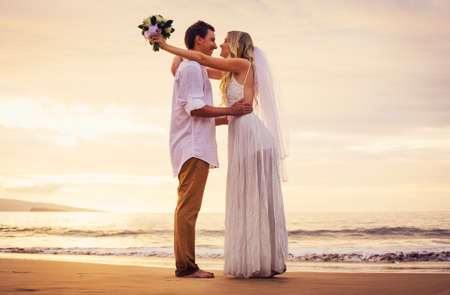 wedding beach: A married couple, bride and groom, at sunset on a beautiful tropical beach