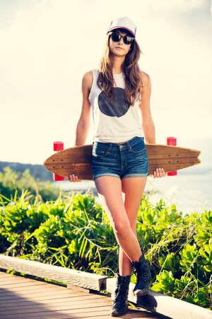 Estilo de vida Moda, Mulher nova bonita com skate, retroiluminado ao pôr do sol