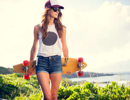 skateboard: Fashion lifestyle, Beautiful young woman with skateboard, backlit at sunset