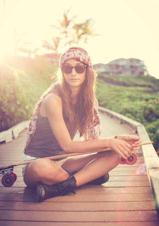 Beautiful young woman posing with a skateboard, fashion lifestyle at sunset  photo