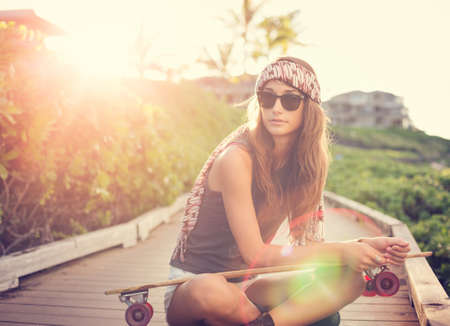 Fashion lifestyle, Beautiful young woman with skateboard, backlit at sunset photo