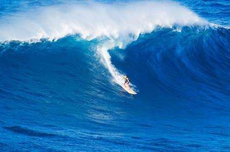 極端なサーファーのライディングの巨大な波